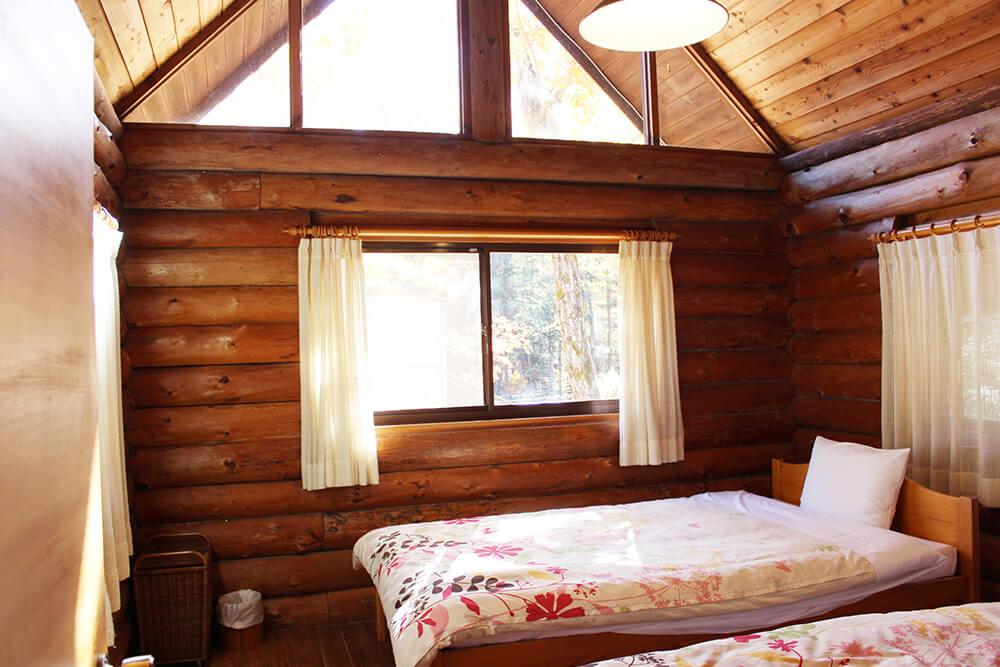 貸別荘ルネス軽井沢の宿泊部屋の葉っぱ柄の掛け布団のあるベッド