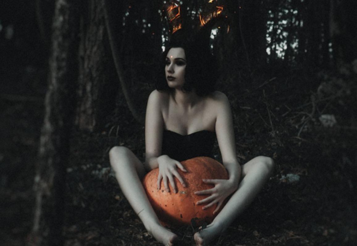 ハロウィンのヘアメイクをしたかぼちゃを抱えた女性