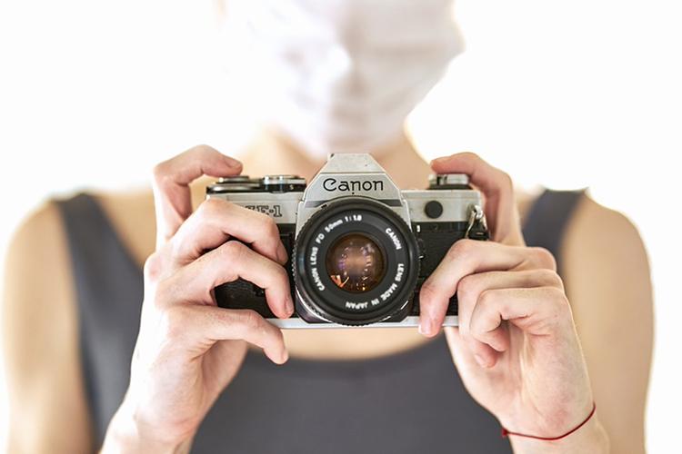 新型コロナウイルス対策でマスクをしてカメラ撮影をするカメラマン