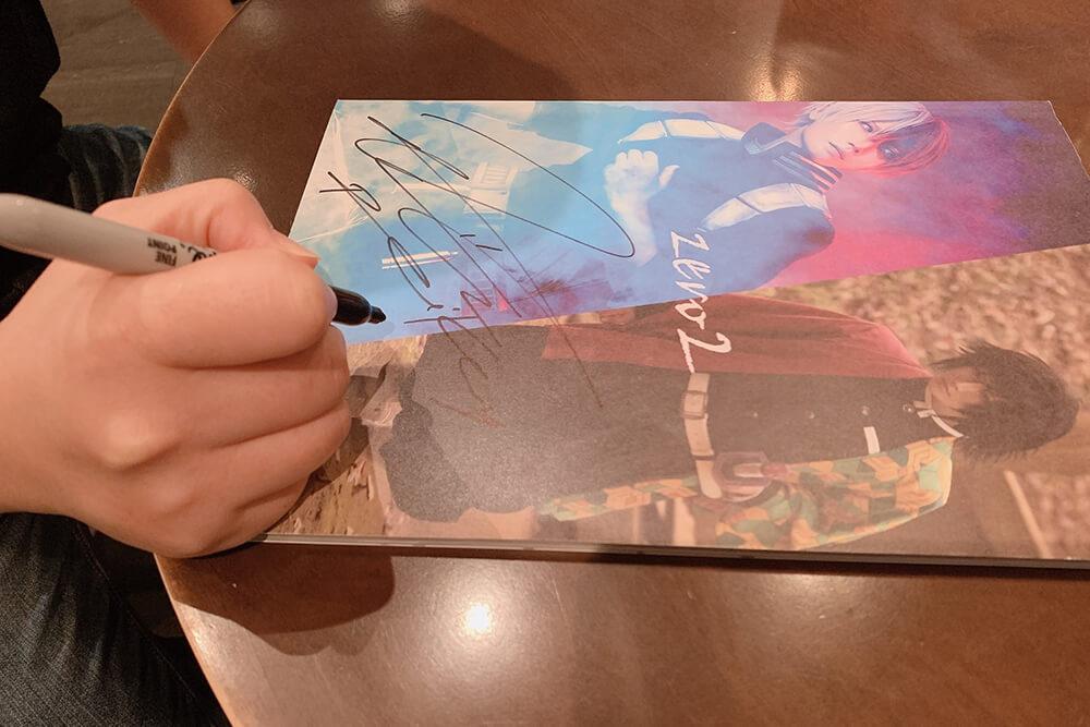 写真集にサインするコスプレイヤー麗華