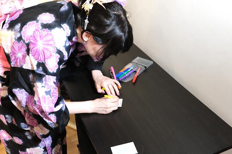 オフ会コスプレイヤーのユリコタイガーさんが撮影したチェキにサインしている様子
